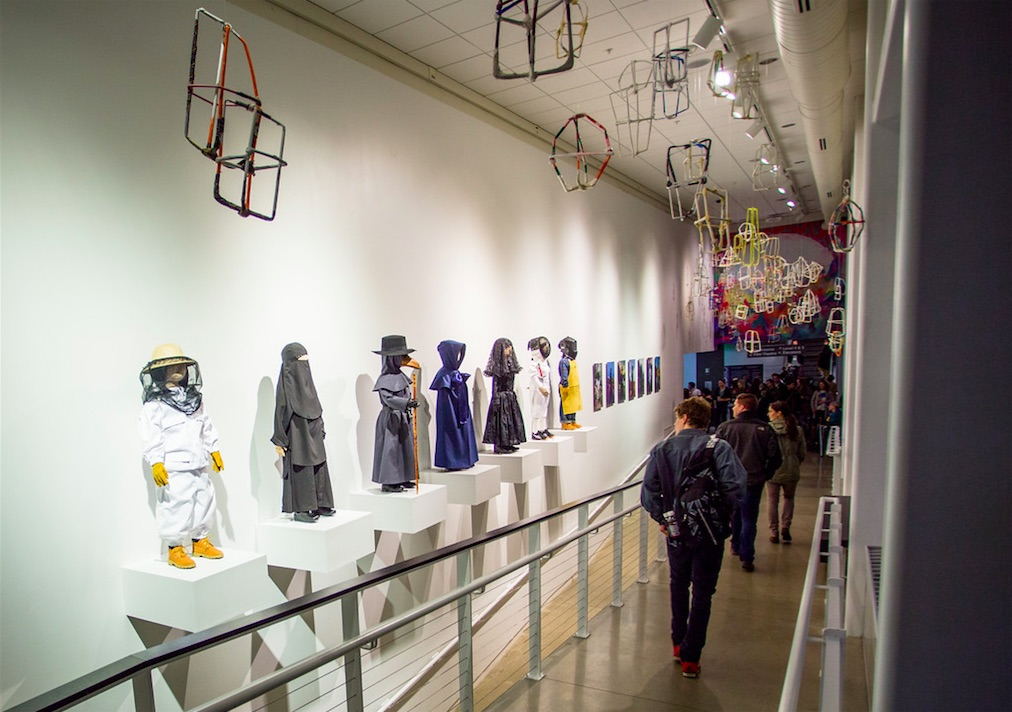 """(above) Jeremy Burleson, Lamps, 2007-2010, Paper, Dimensions variable; (along wall); Laura Swanson, Uniforms, 2015 (""""Beekeeper,"""" """"Burqa,"""" """"Plague Doctor,"""" """"Shaker,"""" """"Mourning,"""" """"Welder,"""" and """"Fencer"""") Altered garments on ready-made mannequins 4' tall each"""
